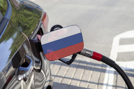 Flag of Russia on the car's fuel tank filler flap. Fueling car with petrol pump at a gas station. Petrol station. Gasoline and oil products. Close up.