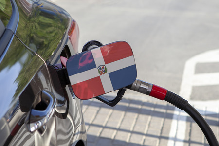 Flag of Dominican Republic on the car's fuel tank filler flap. Fueling car with petrol pump at a gas station. Petrol station. Gasoline and oil products. Close up. Reklamní fotografie
