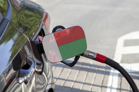 Flag of Madagascar on the car's fuel tank filler flap. Fueling car with petrol pump at a gas station. Petrol station. Gasoline and oil products. Close up.
