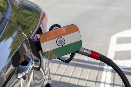 Flag of India on the cars fuel tank filler flap. Fueling car with petrol pump at a gas station. Petrol station. Gasoline and oil products. Close up. Stock Photo