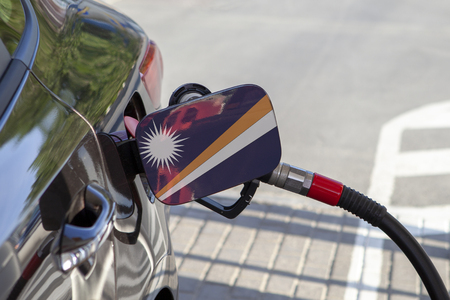 Flag of Marshall Islands on the car's fuel tank filler flap. Fueling car with petrol pump at a gas station. Petrol station. Gasoline and oil products. Close up. Reklamní fotografie