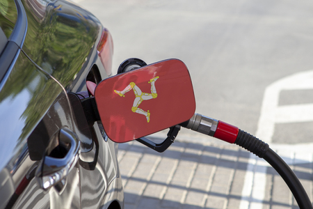 Flag of Isle of Man on the car's fuel tank filler flap. Fueling car with petrol pump at a gas station. Petrol station. Gasoline and oil products. Close up.