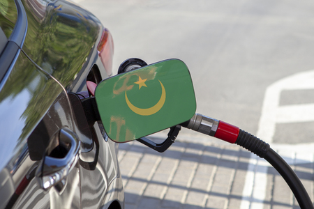 Flag of Mauritania on the car's fuel tank filler flap. Fueling car with petrol pump at a gas station. Petrol station. Gasoline and oil products. Close up.