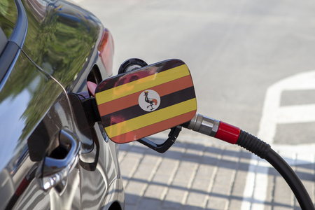 Flag of Uganda on the car's fuel tank filler flap. Fueling car with petrol pump at a gas station. Petrol station. Gasoline and oil products. Close up.