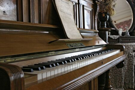 Sizran, Russia, February 10, 2005: Museum, interior of the merchant's living room. Piano with notes. Old musical instrument.