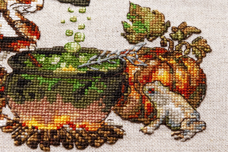 Cross-stitch embroidery with cat in hat, cauldron, toad, bonfire and pumpkin.Part art on mouline threads with grey frog and yellow pumpkin. Close-up. Stock Photo