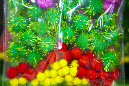 Small multicolored pom-poms with shiny threads in a package. Soft ball. Decoration for home, clothing.  Close up. Stock Photo