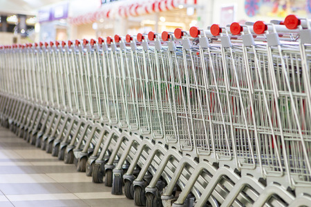 An equal number of shopping carts standing in long rows in the store.