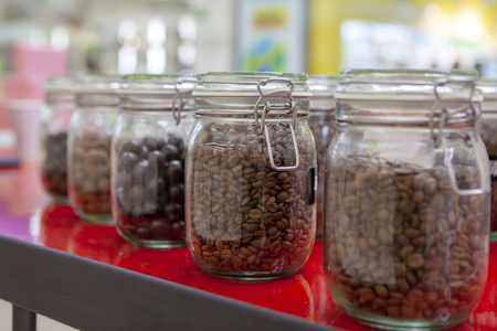 Coffee beans in glass jars on the cafe counter. Bright colors of taste. Stock Photo