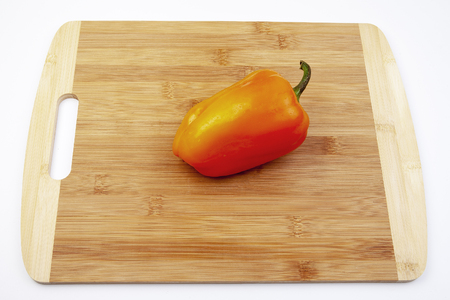Fresh red bell pepper on bamboo cutting board.  Red bright taste.
