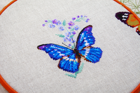 Colorful pattern of butterfly with flower embroidered on fabric close-up