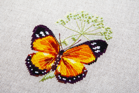 Cross-stitch butterfly with pink wings. Handwork as a hobby.
