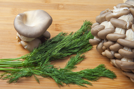 Fresh oyster mushroom clusters laid out on a natural bamboo cutting board. Delicious delicacy giving a special taste to many dishes.