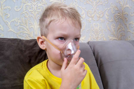 a 5-7 year old boy in a t-shirt takes an inhalation at home