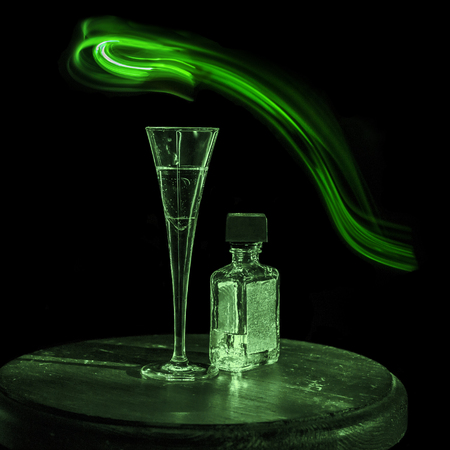 alcohol addiction: A bottle of alcohol,a glass and a green snake as a metaphor for an alcohol addiction, on black background.