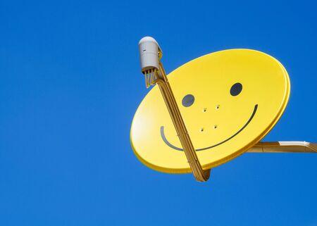 satellite dish: satélite plato amarillo con smiley sobre fondo azul cielo Foto de archivo