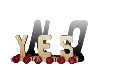 agreeing: Three wooden letters on wheels make the word YES and the shadow of them is NO, isolated on white background