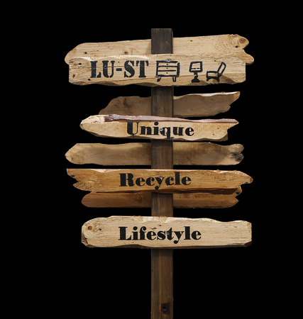 lust: Signpost with the words Lust, Unique, Recycle, Lifestyle printed in black on wooden directional arrows, isolated, on black background, with path.
