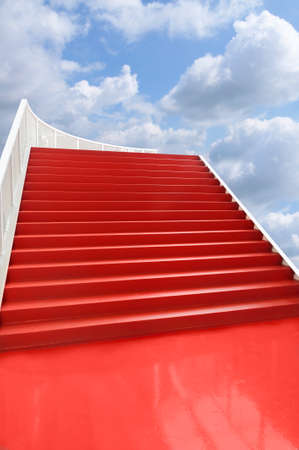 fames: Red carpeted staircase, isolated, on blue clouded sky background.