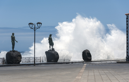 canarias: Very high waves of the Atlantic Ocean, as high as the building and higher than guanche statues on waterfront, Plaza de La Patrona de Canarias, Candelaria, Santa Cruz, the Spanish island of Tenerife. Stock Photo