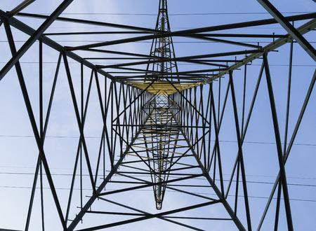 electricity pylon: Geometric pattern of high voltage pylon on blue sky background. Inside electricity pylon looking up.