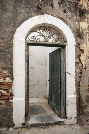 crumbling: An arched doorway in a crumbling stone wall with an old weathered wooden opened door.