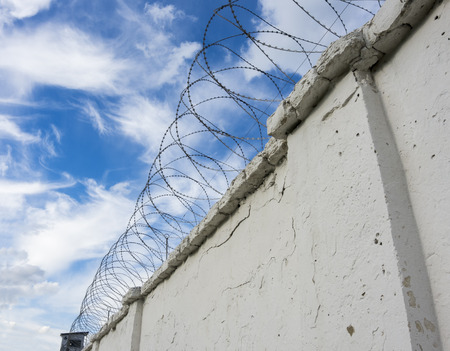 prison wall: Prison wall with barbed wire and a watchtower on blue sky background