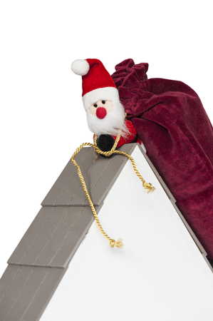 Santa Claus on a roof of a house carrying big sack full of christmas presents, isolated, on white background
