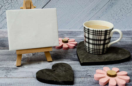 Cup of coffee, small easel with a blank canvas over white, two dark wooden hearts and pink flowers. Old wooden background and big copy space for your sign and text Stock Photo