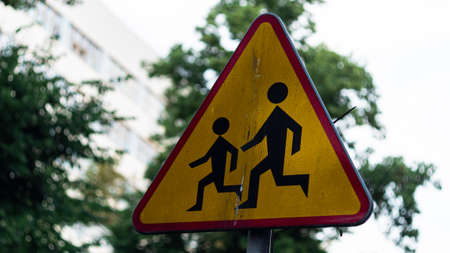 A red and yellow sign with a picture of an adult helping a child across the street