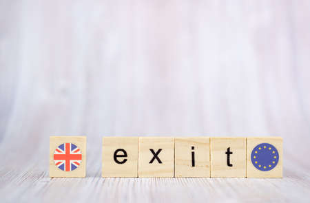 Brexit concept .Exit word written on wood blocks with British and EU flags. Exit text on wooden table for your desing 免版税图像