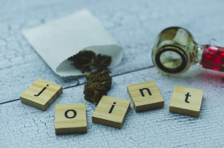 Marijuana cones in a white paper pharmacy bag against a glass Smoking pipe. Wooden cubes with the word JOINT