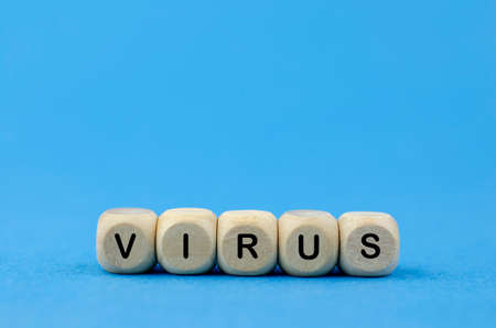 The word Virus on wooden cubes, blue background. Medical concept.