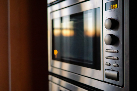 evening sun reflicting of stainless steel microwave oven door closeup Imagens