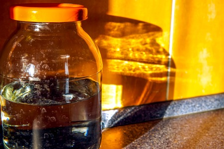 Glares of the evening sun refracted through the water in a jar