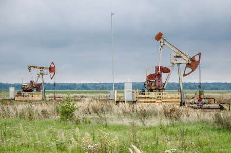 Pump jack with a derrick drilling a new well in the background.