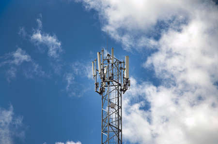 Telecommunications tower with 4G, 5G transmitters. cellular base station with transmitting antennas on a telecommunications tower against the blue sky. Foto de archivo