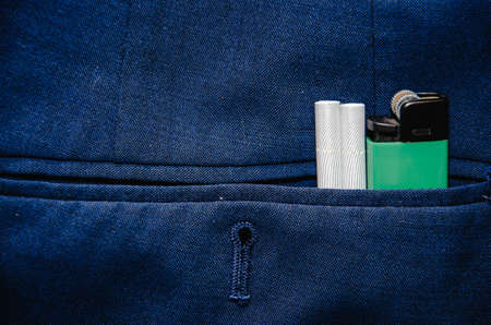 Green gas lighter in the back pocket of blue womens jeans. Concept of smoking woman, cigarette smoking. Standard-Bild