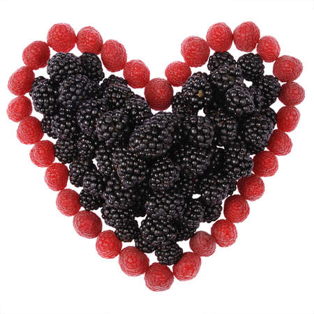 Heart made out of raspberries and blackberries on white background