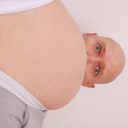 Surprised by her husband looks out the stomach of his pregnant wife on grey background Stock Photo - 13366491