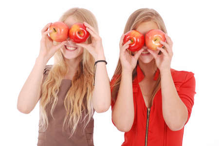 eye red: Two girls hold near eyes fresh apples isolated on white Stock Photo