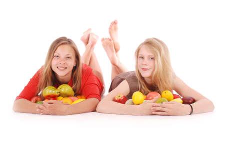 apple and orange: Two girls holding fresh fruits isolated on white