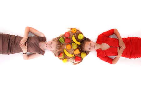 ni�o modelo: Retrato de dos ni�as con pelos y frutas entrelazados, aislado en blanco Foto de archivo