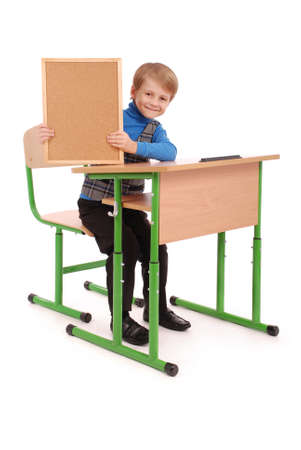 6 7 years: Boy sitting at a school desk and holding board isolated on white