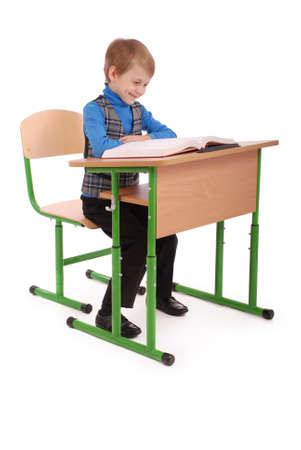 6 7 years: Boy sitting at a school desk isolated on white