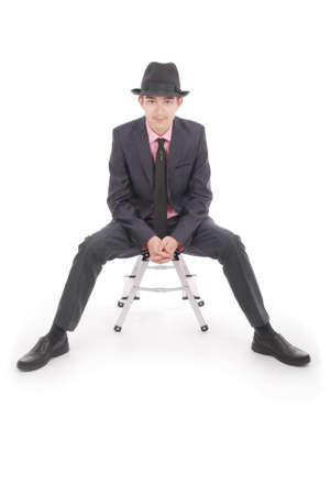 only one teenage boy: Boy in black suit sits on a chair isolated on white