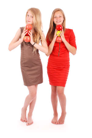 3 persons only: Two young girl holds an three apples isolated on white