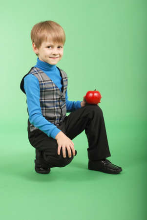 6 7 years: Boy holding a red apple isolated on green
