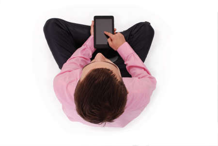 only one teenage boy: Boy in pink shirt sit and hold tablet PC isolated on white. Shallow depth Stock Photo