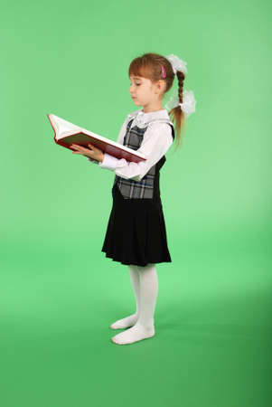 Girl in school uniform reading a book isolated on green Stock Photo